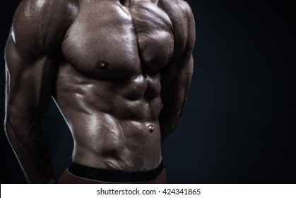 torso of attractive male body builder on dark blue background.