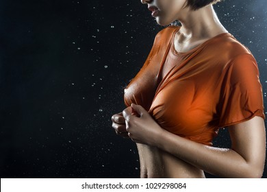 Torso of a big breasted girl wearing wet shirt on a dark background with falling rain drops and scenic smoke. Advertising, commercial Design. Copy space. Mixed asian-caucasian race.