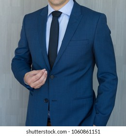 Torso of a businessman standing, making italian hand gesture, wearing navy blue suit against grey backgound.