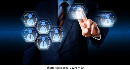 Torso of a consultant is dismantling a work team in cyber space. His left hand is moving a female and a male worker icon away from the group in a swiping gesture with raised index and middle finger.