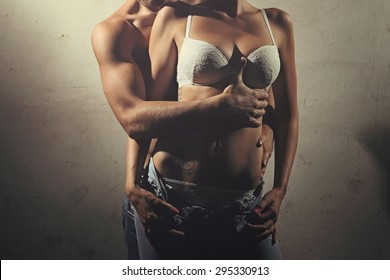 Torso detail of shirtless couple against old wall . Fashion and sensual portrait
