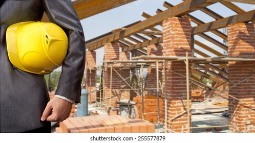 torso of engineer worker holding in hands yellow plastic helmet hardhat for workers security on background of  new metal red brick roof and blue summer sky with clouds Empty space for inscription