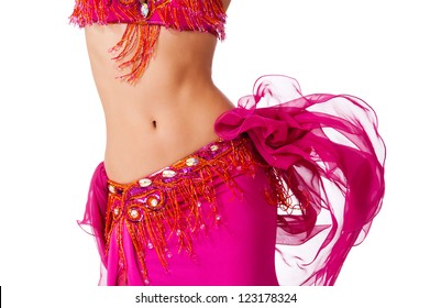 Torso of a female belly dancer wearing a hot pink costume shaking her hips. Isolated on white.