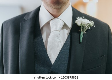 The torso of a groom dressed with a black wedding suit