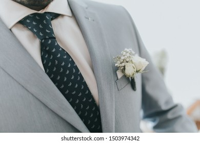 The torso of a groom dressed in a wedding suit