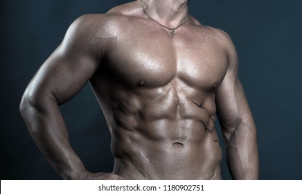 Torso of handsome, strong and sexy male fitness model/bodybuilder poses on dark background