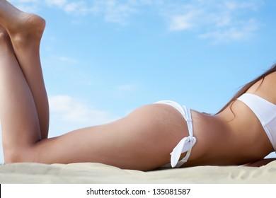 Torso and legs of luxurious woman in white bikini sunbathing
