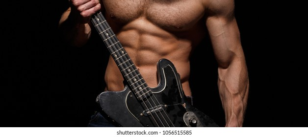 Torso man. Chest muscles, Six pack, ab, triceps. Electric guitar. Music festival. Instrument on stage and band. Strong, muscular, muscles man, bodybuilding. Music concept. Play the guitar.