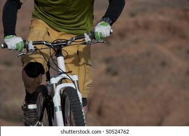 The torso of a man riding a mountain bike in a desert landscape. Horizontal shot.
