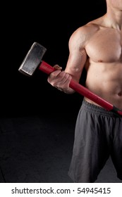 Torso of a shirtless guy holding a sledgehammer