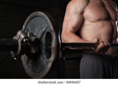 Torso of a shirtless guy lifting weights