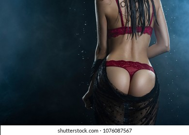Torso of slim girl wearing a red lingerie and black veil posing from her back in rain water drops in a studio shows her beautiful butt on black in a theatrical smoke. Healthy smooth skin. Copy space