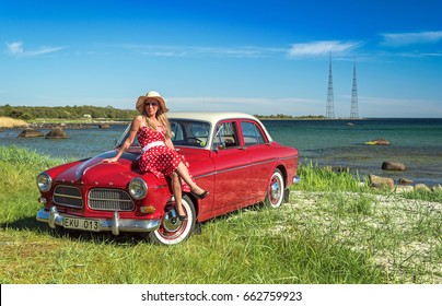 TORSO, SWEDEN -MAJ 21: Spring portrait of woman with Swedish retro car on the sea coast in Sweden, in Maj 21, 2017. The Volvo Amazon was a mid-size car manufactured by Volvo Cars from 1956 to 1970.