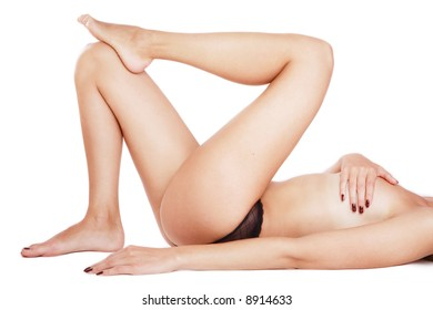 Torso of tanned slim woman with beautiful long legs lying on white background