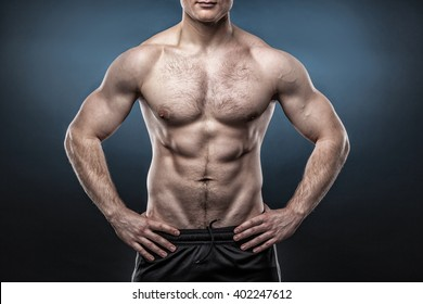Torso of young muscular man isolated on dark blue background