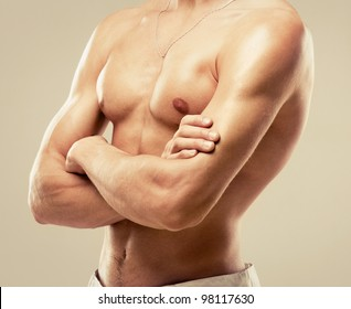 torso of a young muscular man, isolated on brown studio background