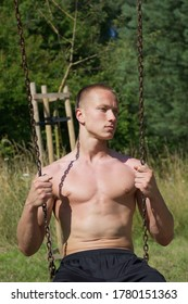 Torso of young muscular shirtless man sitting outdoor and holding chain from swing.