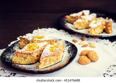 Torta di riso - classical Italian dessert. Rice cake with almonds, candied orange peels and amaretto. A slices of rice cake with almond cookies in a plate. Italian food. Selective focus.