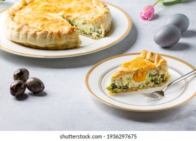 Torta Pasqualina. Traditional Italian savory Easter pie with spinach, chard, ricotta and whole eggs on gray background.