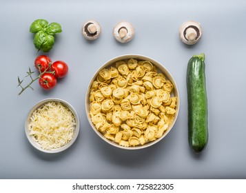 Tortellini bowl with zucchini, mushrooms and vegetarian cooking ingredients on kitchen table background with cutting board , top view, flat lay. Healthy cooking and eating. Italian food concept