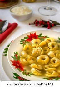 Tortellini in broth. Italian Christmas lunch. Parmigiano in background