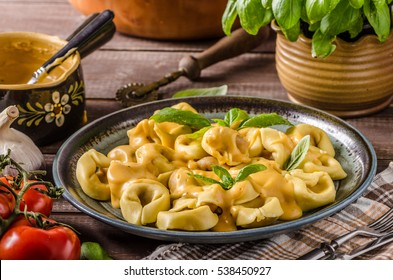 Tortellini with cheese sauce, basil and herbs