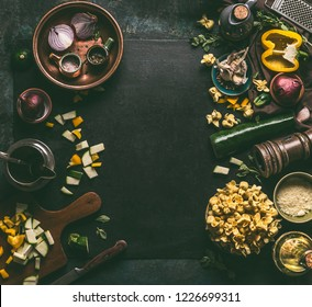 Tortellini food background.  Fresh homemade vegetarian tortellini cooking preparation on dark rustic table with vegetables ingredients and vintage  kitchen utensils, top view. Home cuisine.