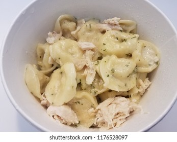 tortellini pasta with cheese and sauce with chicken in white bowl