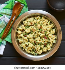 Tortellini salad with green peas, fried bacon and parsley in big salad bowl, with small rustic bowls, wooden spoon and fork on the side, photographed overhead on dark wood with natural light