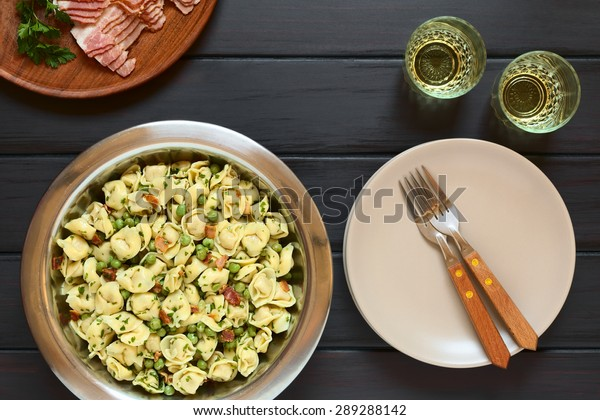 Tortellini salad with green peas, fried bacon and parsley in big salad bowl, with plates, forks and two glasses of white wine on the side, photographed overhead on dark wood with natural light