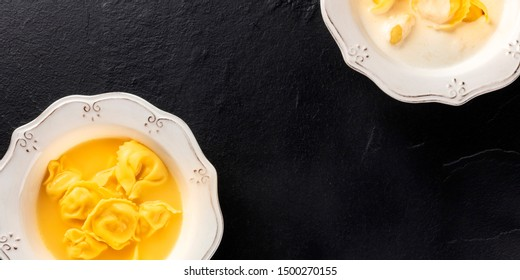 Tortellini served with broth and cream sauce, Italian food on a black background with a place for text, overhead panoramic shot