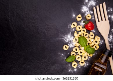 Tortellini, tomato, basil, olive oil bottle and a wooden spoon on a black stone plate. Top view with copyspace