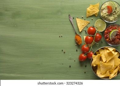 Tortilla chips arranged on wooden surface with guacamole and salsa