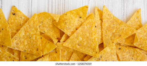 Tortilla chips on white wooden surface, top view. Mexican food.