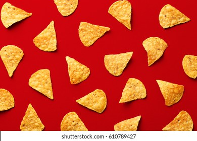 Tortilla chips pattern on a red background. Repetition concept. Top view