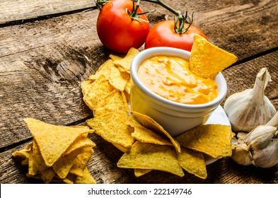Tortilla chips with tomato and cheese-garlic dip on wood old table