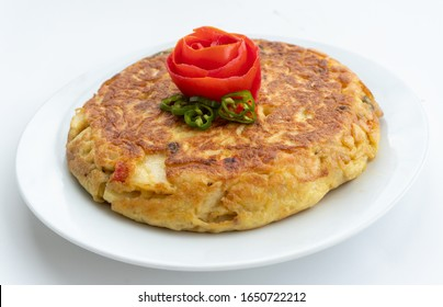 Tortilla espanola, spanish omelette with potatoes with a tomato flower on top