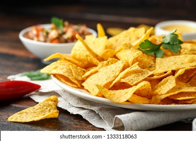 Tortilla nachos chips with cheese sauce, guacamole and tomatoes salsa dip. lime. chilli pepper.