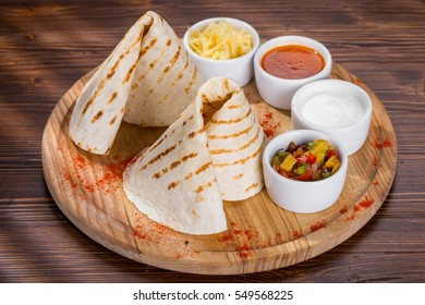 Tortilla on cutting board with assortment of sauces.