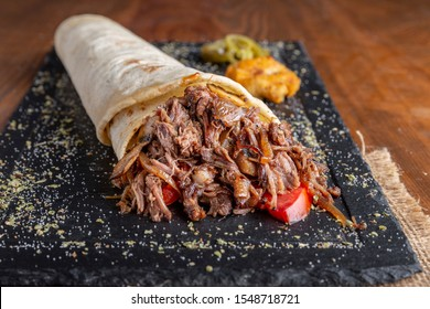 Tortilla with pulled beef meat, onion and tomato serving on black plate with humus and jalapeno pepper. - Shutterstock ID 1548718721