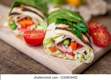 tortilla  salad ingredients and pepper on a wooden cutting board