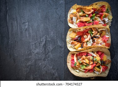 Tortilla sandwiches with chicken meat in bbq sauce on dark background with blank space