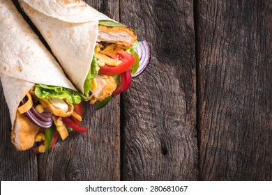 Tortilla sandwiches with fried chicken and vegetables on wooden background with blank space