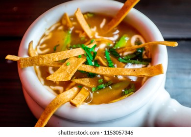 Tortilla soup, with tomato and condiments in a white bowl.