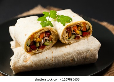 Tortilla with vegetables and hummus with chickpeas. Front view.