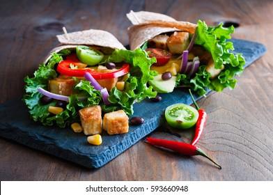Emballage de tortilla ou burrito avec du tofu, des verts et des légumes, une nourriture végétarienne saine, image tonique