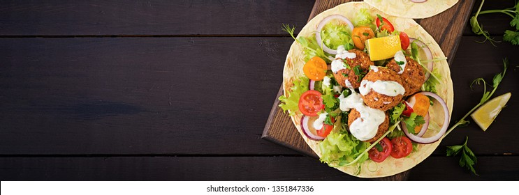 Tortilla wrap with falafel and fresh salad. Vegan tacos. Vegetarian healthy food. Banner. Top view