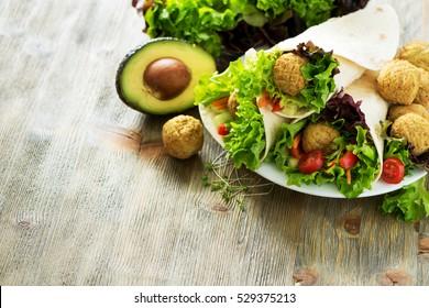Tortilla wrap with falafel and fresh salad, vegetarian healthy food, vegan concept copy space