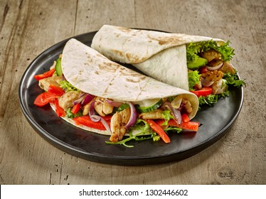 Tortilla wrap with fried chicken meat and vegetables on wooden table