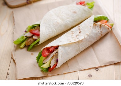 tortilla wrap with grilled chicken,avocado,tomato and lettuce on paper
